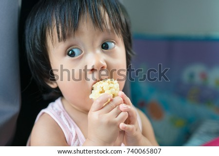 Asian baby eating corn and holding it by himself in day time