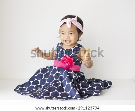 Asian Baby girl dressed and wearing headband - stock photo
