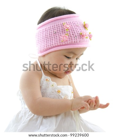 Asian baby girl playing with her hand - stock photo