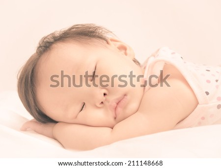 Asian baby girl sleeping on bed with vintage filter