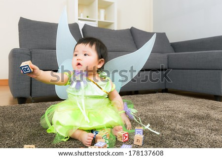 Asian baby girl with halloween party dressing and play toy block - stock photo
