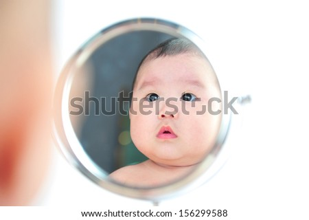 asian baby girl with mirror on white background - stock photo