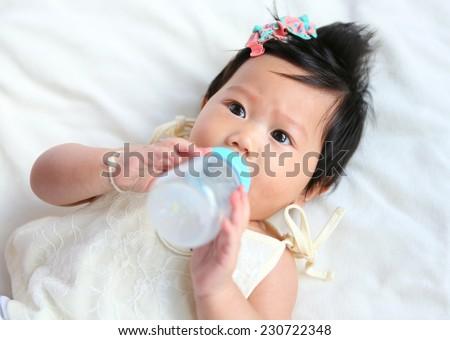 Asian baby infant eating milk from bottle - stock photo