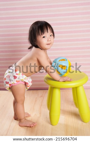 Asian baby infant standing. Cute child playing with her toys against green chair. Isolated on pink wooden background - stock photo