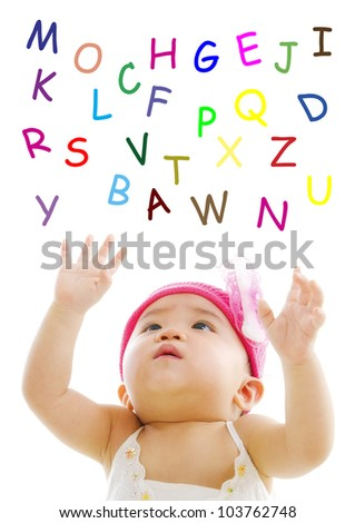 Asian baby is trying to reach alphabet words - stock photo