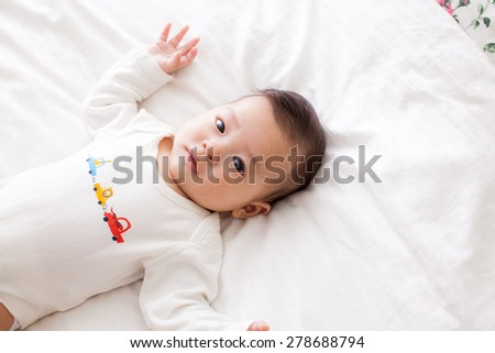 asian baby lay down on bed - stock photo