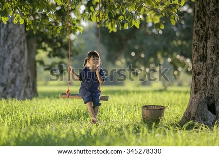 Asian baby sleeping on swing in the rice farm. - stock photo