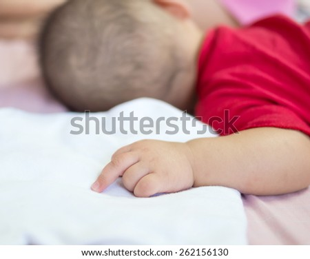 Asian baby sleeping on the bed with middle finger - stock photo