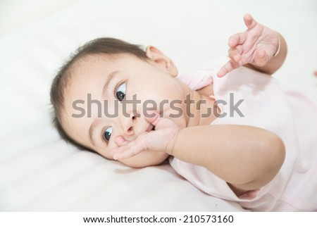 Asian baby sucks his fingers