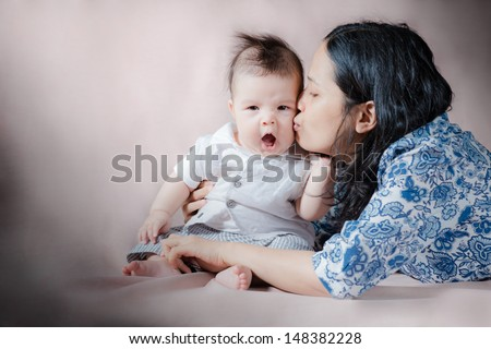 Asian baby surprised with a kiss from mom - stock photo