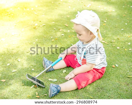 Asian baby taking selfie photo on the green grass field in the park - stock photo