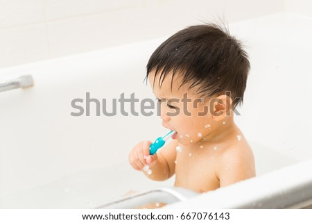 Asian baby uses toothbrush in the bathroom