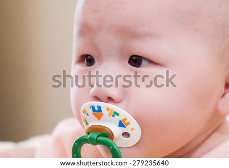 asian baby with a pacifier - stock photo