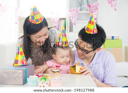 asian baby with family celebrating baby birthday party