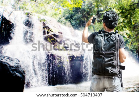 Asian backpacker travel with mobile for search destination to waterfall Pangsrida,Srakeaw,Thailand