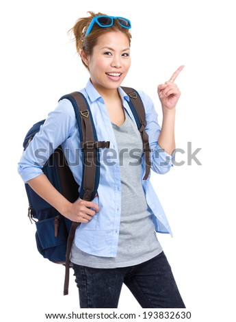 Asian backpacker with finger pointing up - stock photo
