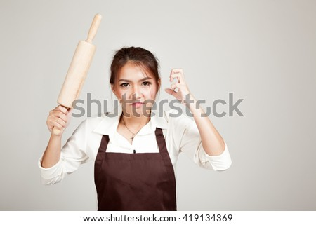 Asian Baker woman  in apron  with wooden rolling pin on gray background