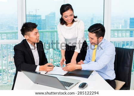 Asian banker counseling client finance investment in bank office