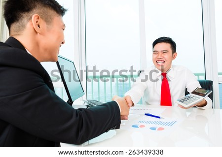 Asian banker offering client finance assets in bank office  - stock photo