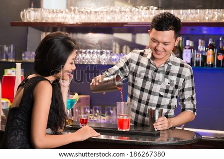 Asian barman mixing a drink to a girl