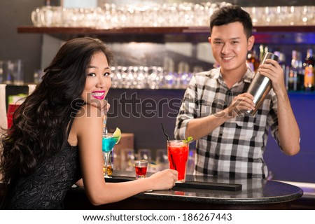 Asian barmen serving drinks to the woman