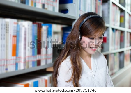Asian beautiful female student listen to music in library - stock photo