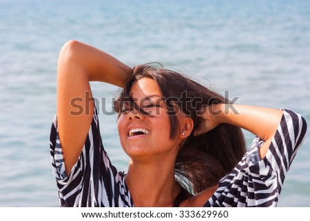Asian beautiful girl smiling happy on beach vacation enjoying warm sunshine. Mixed race Asian Caucasian pretty model outside with sun in background on Hawaiian tropical beach. - stock photo