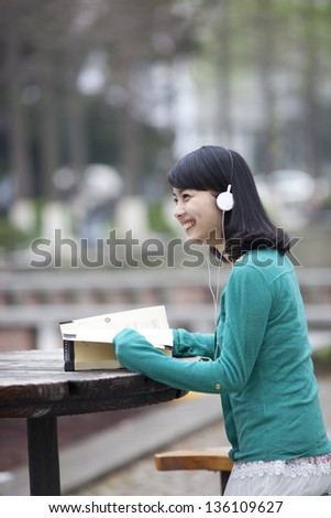 Asian beautiful student reading book in campus with earphone