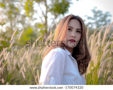 Asian beautiful Woman in the Meadow, wearing white shirt, On a sunny days. sexy woman concept.