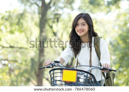 Asian Beautiful woman looking camera with attractive smiling at park. Woman ride a bicycle at park. People lifestyle concept.