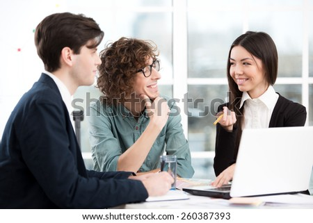 Asian beautiful young businesswoman and two businessmen working with laptop. Office interior with window. Concept for teamwork