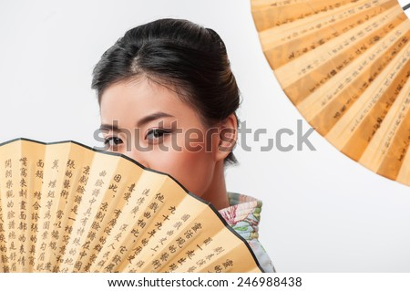 Asian beauty. Attractive Asian woman wearing Japanese kimono hiding behind traditional fan while standing against white background with hand fan  - stock photo