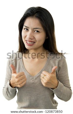 asian beauty with braces shows two thumbs up - stock photo