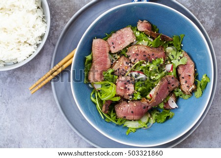 Asian beef salad with cucumber and herb salad and black and white sesame seeds