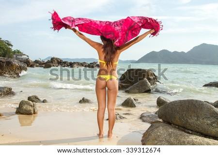 Asian bikini model with sarong on the beach - stock photo