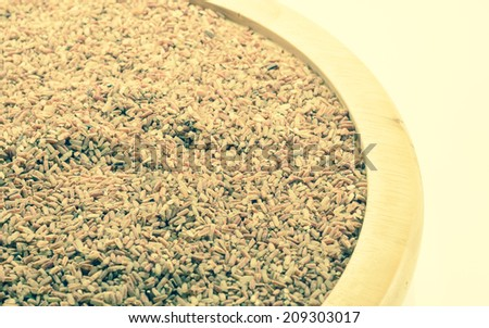 asian Black rice (Berry rice) at wood plate on white background with retro filter.