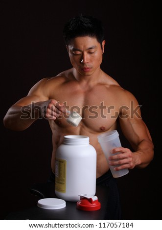 Asian Body Builder pouring a scoop of protein mix in to a mixing jar - stock photo