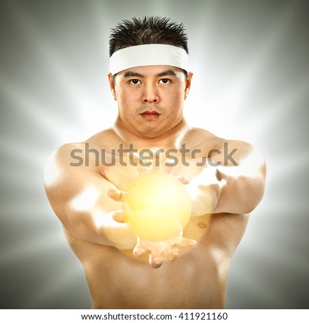 asian body builder with energy in his hands on grey background - stock photo