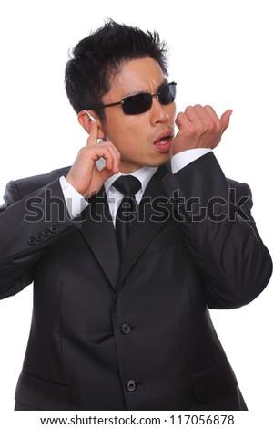 Asian Bodyguard talking in microphone listening to earpiece - stock photo
