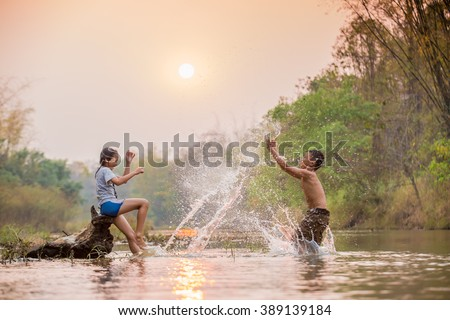 asian boy and girl playing in the river - stock photo