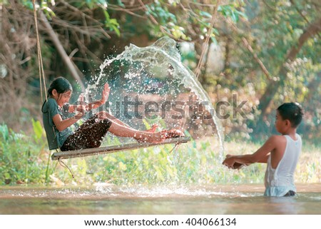 asian boy and girl playing in the river