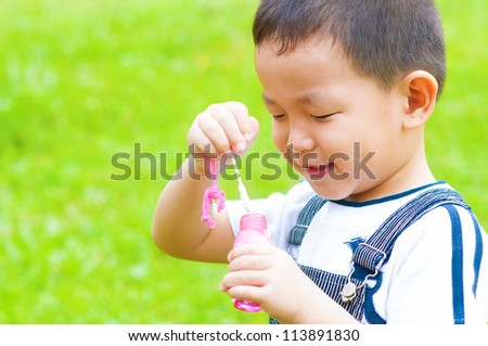 Asian boy blowing bubbles outdoor - stock photo