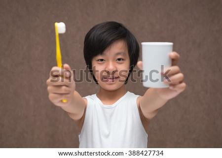 Asian boy brushing teeth - stock photo