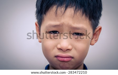 Asian boy crying over dark background - stock photo