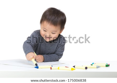 Asian boy drawing with crayon - stock photo