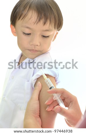 Asian boy during medical injection on white background. - stock photo