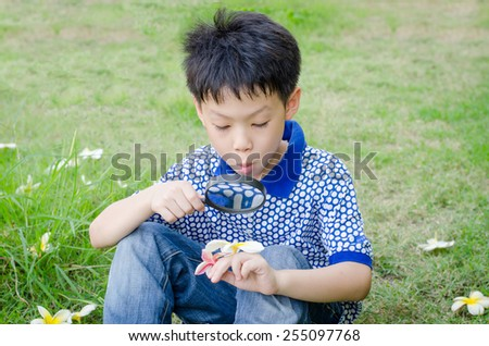 Asian boy exploring the environment with a magnifying glass - stock photo