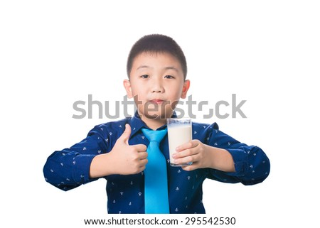 Asian boy giving you thumbs up with glass of milk in hand, isolated on white background. - stock photo