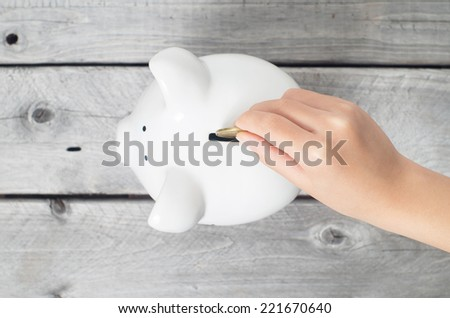 Asian boy hand dropping a coin into white piggy bank against wooden grey background - stock photo