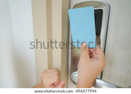 Asian boy hand hold card to open / close for door access control scanning key card to lock and unlock door. Security door system concept.